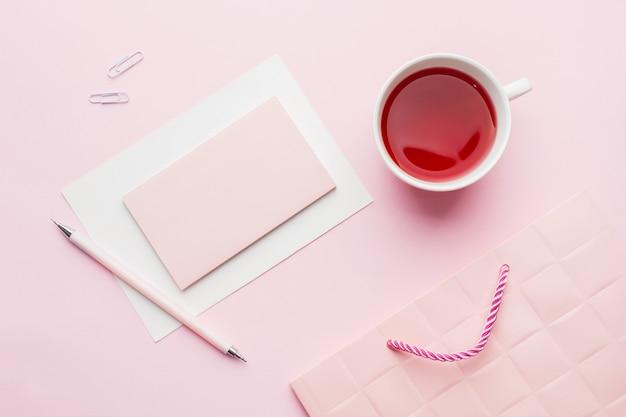 Rood-roze objecten. kopje thee en kladblok voor tekst op pastel roze achtergrond.