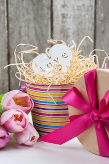 Rood roze tulpen en geschenkdoos met rood lint