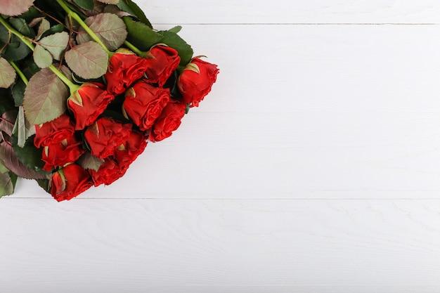 Rood rozenboeket op een witte houten lijst