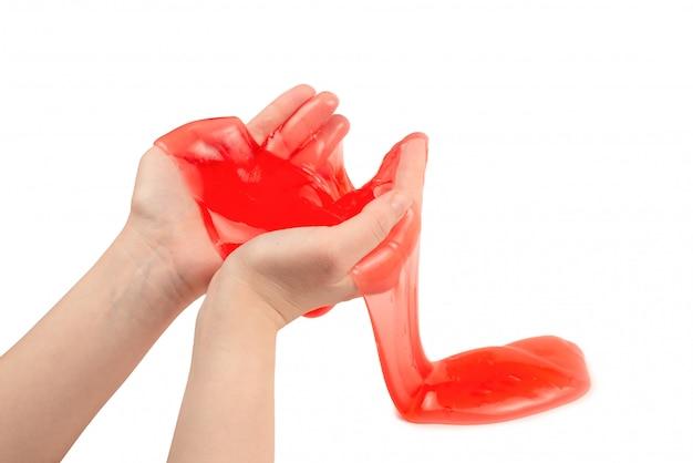 Rood slijmstuk speelgoed in vrouwenhand dat op wit wordt geïsoleerd.