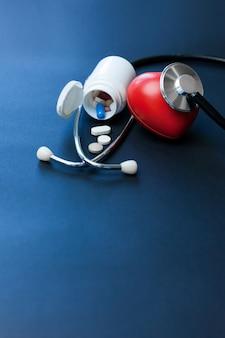 Rood stuk speelgoed hart en stethoscoop die op donkerblauwe oppervlakte leggen