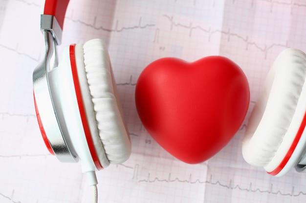 Rood stuk speelgoed hart hoofdtelefoons op papier cardiogram