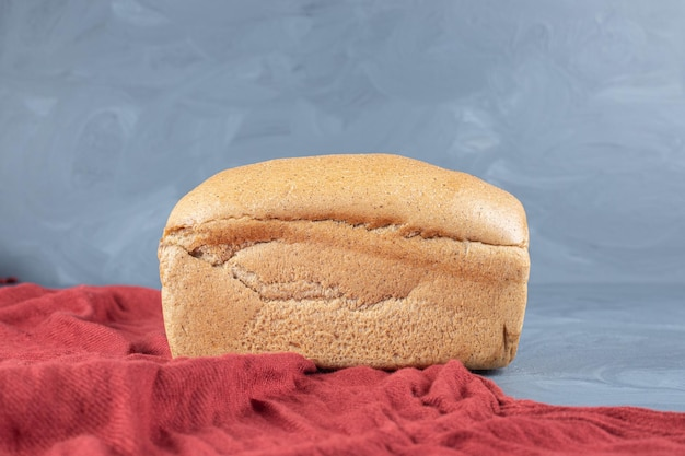 Rood tafelkleed onder een blok brood op marmeren tafel.