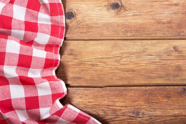 Rood tafelkleed op oude houten tafel, bovenaanzicht