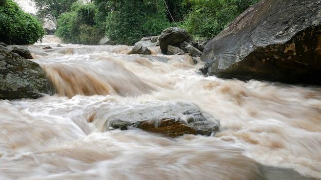 Rood troebel water stroomt naar beneden van de berg als gevolg van hevige regen