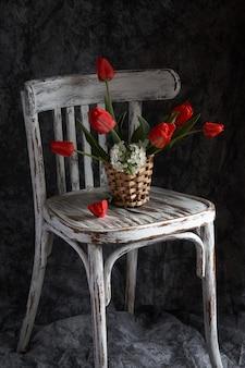 Rood tulpenboeket in houten vaas op uitstekende stoel