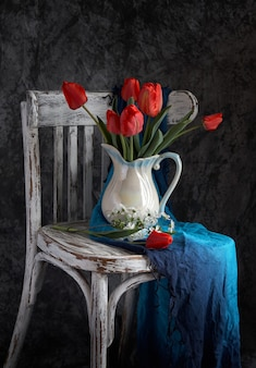 Rood tulpenboeket in witte vaas op wijnoogst