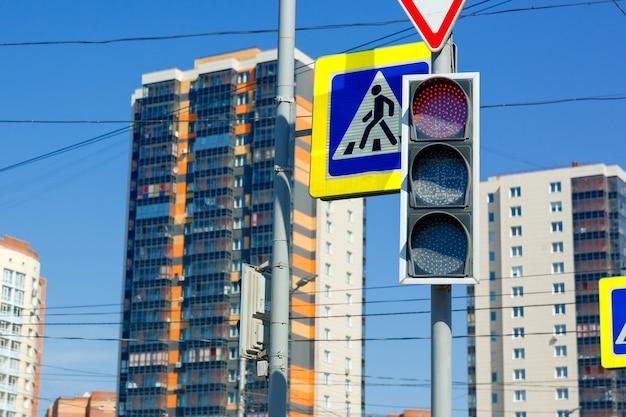 Rood verbodssignaal van verkeerslicht op de achtergrond van hoogbouw