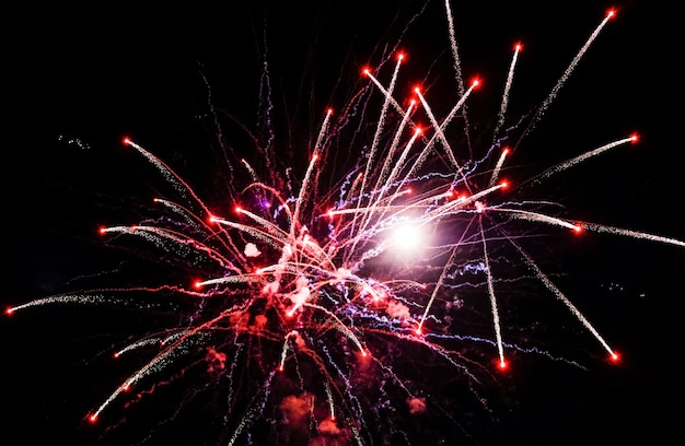 Rood vuurwerk in de lucht op zwarte achtergrond