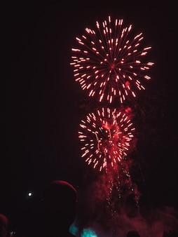 Rood vuurwerk op de nachtelijke hemel