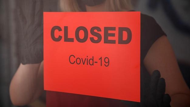 Rood waarschuwingsbord gesloten covid 19 lockdown op de voordeur als nieuwe normale sluiting in restaurant. vrouw met beschermende medische maskerhandschoenen hangt een gesloten bord aan het raam van een leeg café.