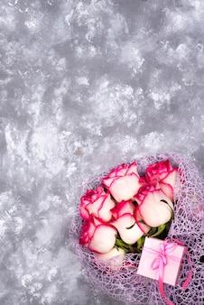 Rood wit roze bloemboeket met roze giftdoos op steenlijst.