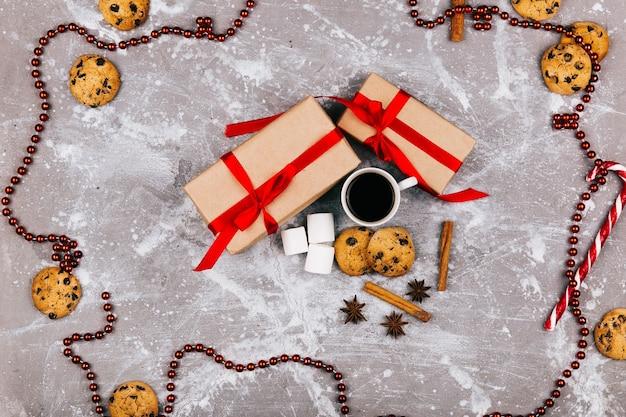 Rood wit suikergoed, koekjes, heemst, kop van koffie en huidige doos liggen op grijze vloer