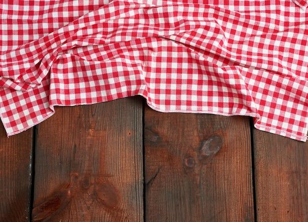 Rood-witte textiel keukenhanddoek op een bruine houten tafel