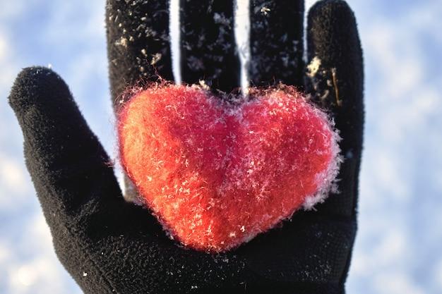 Rood wollen hart bedekt met sneeuwvlokken ligt op een handpalm in een zwarte handschoen