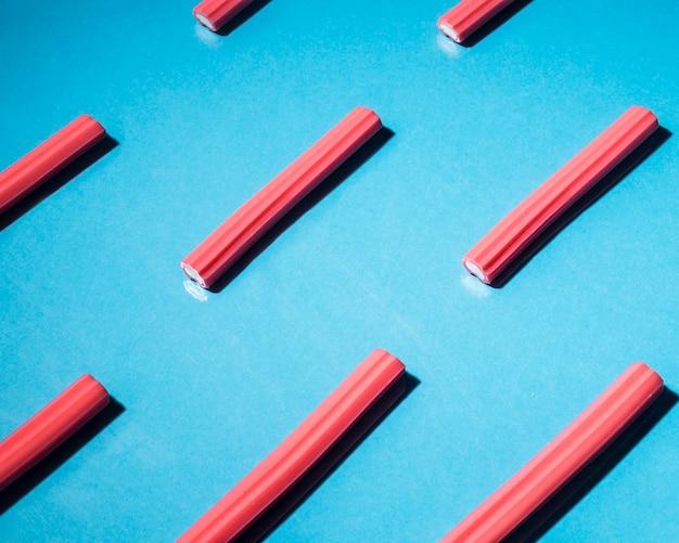 Rood zacht zoethoutsuikergoed dat op blauwe achtergrond wordt geschikt