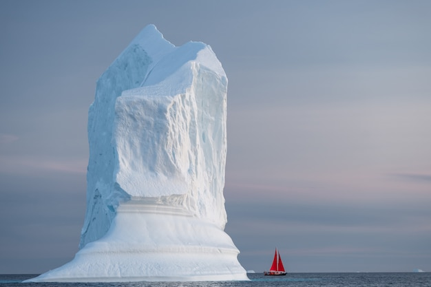 Rood zeil met grote gletsjer en ijsberg