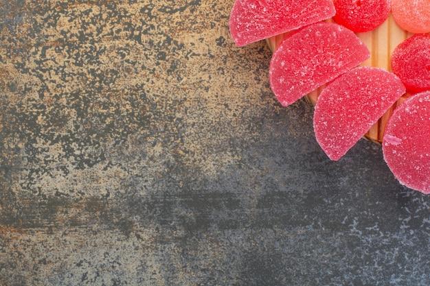 Rood zoet geleisuikergoed op houten plaat