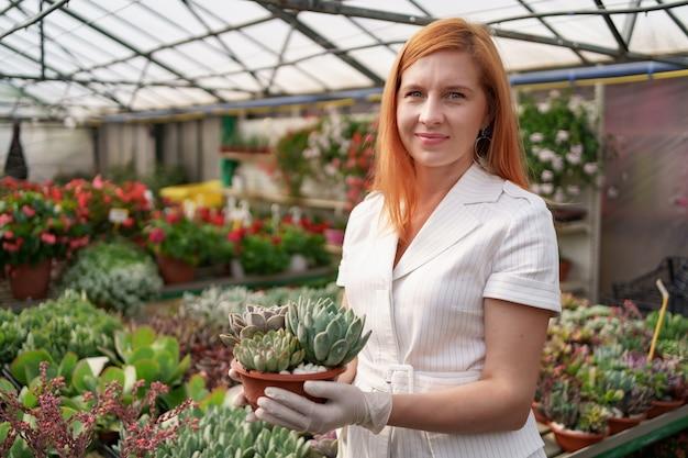 Roodachtig vrouwenportret die rubberhandschoenen en witte kleren dragen die vetplanten of cactussen in potten met andere groene installaties houden