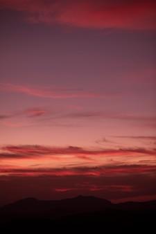Roodachtige bewolkte achtergrond aan de hemel