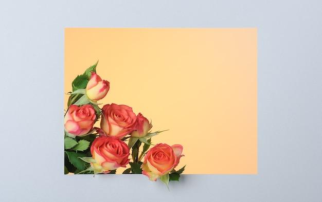 Roodgele rozen in rechthoekig papier grijs frame op geel oppervlak