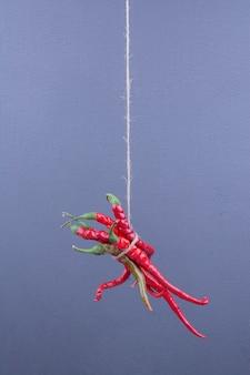 Roodgloeiende chili pepers opgehangen op blauw.