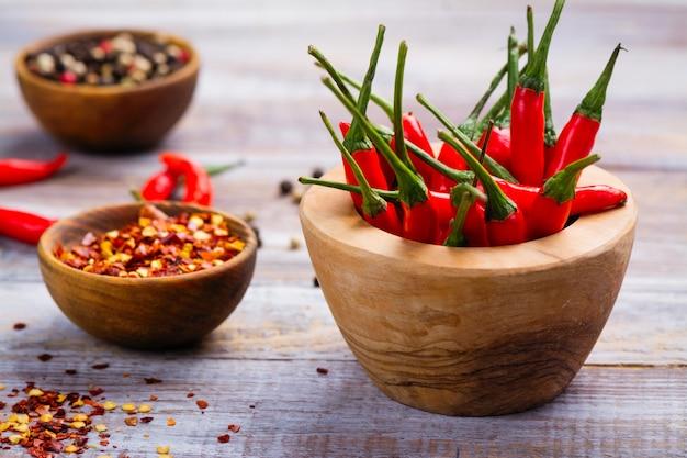 Roodgloeiende chilipepertjes in een houten vijzel, pepervlokken en peperkorrels in houten kommen