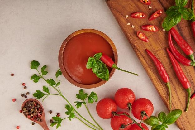 Roodgloeiende chilisaus. tomatenketchup, chilisaus, puree met chilipeper, tomaten en knoflook. op houten snijplank op stenen oppervlak. bovenaanzicht.