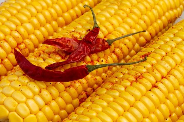 Roodgloeiende de spaanse peperspeper van de close-up met maïs
