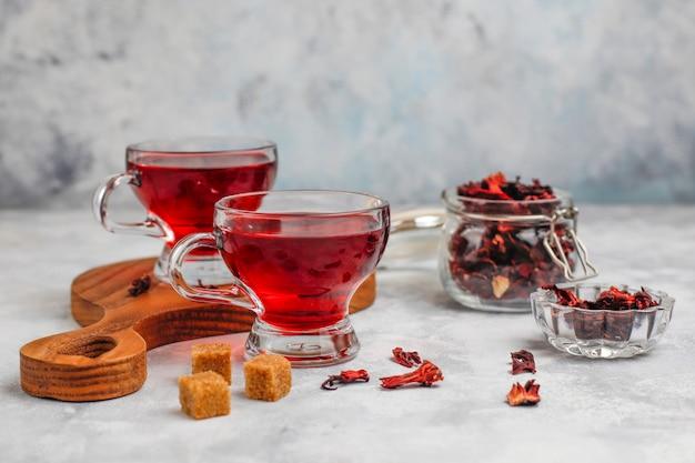 Roodgloeiende hibiscus-thee in een glazen mok op beton met droge hibiscusbloemblaadjes
