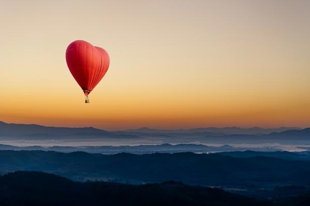 Roodgloeiende luchtballon in de vorm van een hart dat over de berg vliegt