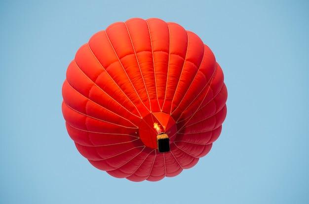 Roodgloeiende luchtballon in een heldere blauwe hemel.