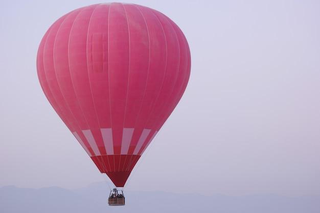 Roodgloeiende luchtballon met toeristen die in de ochtendhemel vliegen. lancering van een heteluchtballon in de vroege ochtend. spectaculaire ochtendscène.