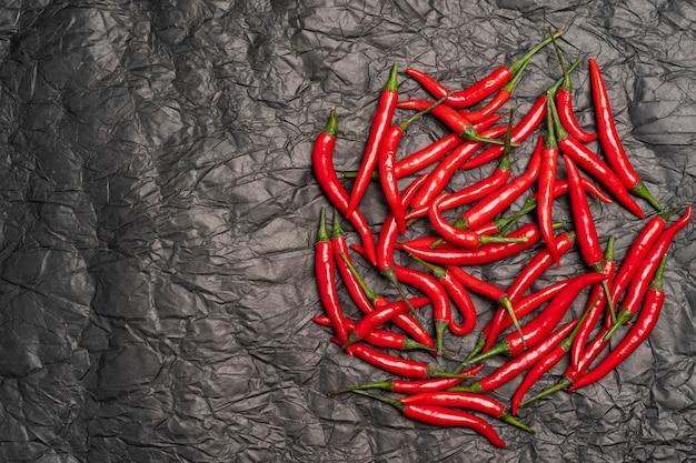 Roodgloeiende peper gestrooid op zwart verfrommeld papier