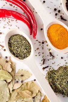 Roodgloeiende pepers en andere soorten kruiden in lepels op wit
