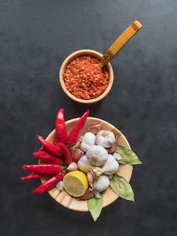 Roodgloeiende saus, knoflook, rode peper en kruiden op een zwarte tafel. bovenaanzicht