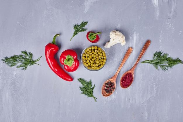 Roodgloeiende spaanse pepers met erwten en kruiden in houten lepels.