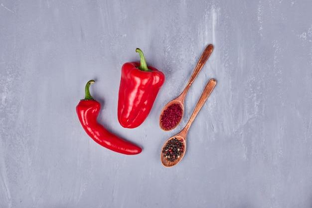 Roodgloeiende spaanse pepers met paprika en peper in houten lepels.