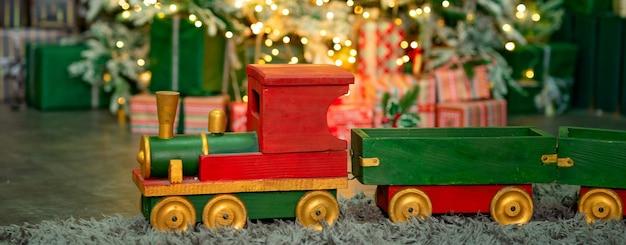 Roodgroene houten trein onder de kerstboom prettige kerstdagen en gelukkig nieuwjaar concept