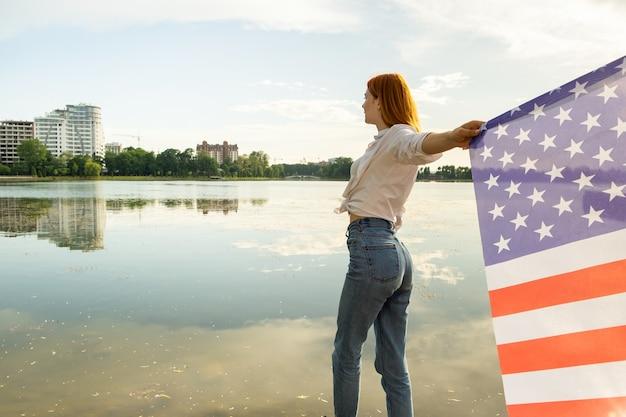 Roodharig meisje dat de nationale vlag van de vs in haar handen houdt. positieve jonge vrouw die de onafhankelijkheidsdag van de verenigde staten viert.
