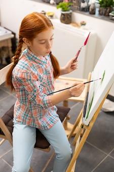 Roodharig meisje dat haar schilderende penseel inkleurt
