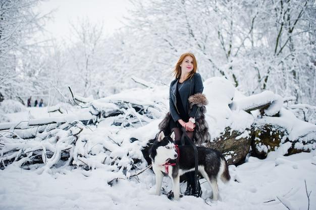 Roodharig meisje die bij park met schor hond op de winterdag lopen.