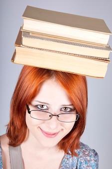 Roodharig meisje houdt boeken op haar hoofd.