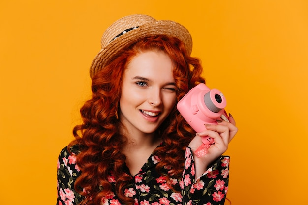 Roodharig meisje in bloemenprintblouse en blouse knipoogt en houdt roze camera op oranje ruimte.