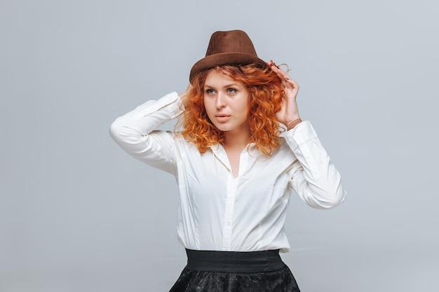 Roodharig meisje in bruine hoed en wit overhemd