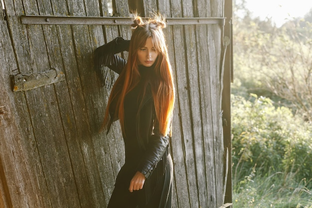 Roodharig meisje in een zwart lederen jas bij zonsondergang tegen een houten oude deur