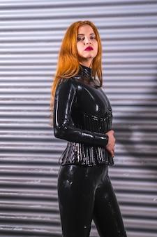Roodharig meisje in latex, een zwarte top en een strakke broek, op een metalen achtergrond, die het stopgebaar maakt