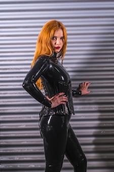 Roodharig meisje in latex, een zwarte top en strakke broek, op een metalen achtergrond, leunend tegen de muur op zoek naar