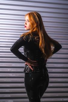 Roodharig meisje in latex, een zwarte top en strakke broek, op een metalen achtergrond, poseerde op haar rug