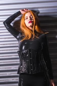 Roodharig meisje in latex, een zwarte top en strakke broek, op een metalen achtergrond